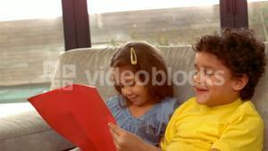 Hispanic children reading together a book