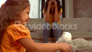 Hispanic children disputing while the mother takes her hands over her head