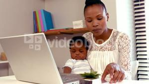 Serious mom with baby working