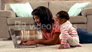 Mother using computer with her baby