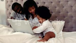 New parents with their baby in bed