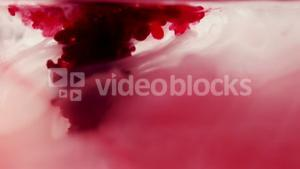 Red and purple ink swirling in water