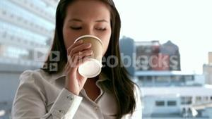 Businesswoman having coffee to go outside