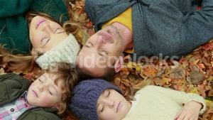 Family lying on autumn leaves in park