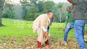 Happy family tossing autumn leaves