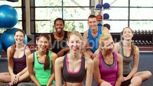 Fit people smiling at camera in gym