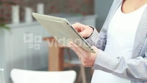 Pregnant asian woman using tablet pc
