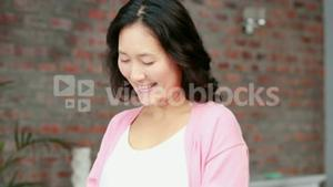 Pregnant asian woman using her phone
