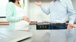Pregnant couple fighting in the kitchen