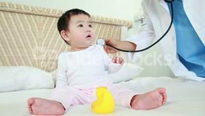 Doctor examining baby on bed