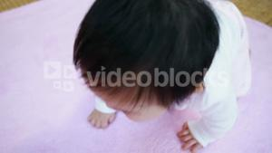 Asian baby crawling on blanket