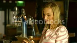 Woman using her tablet at the bar