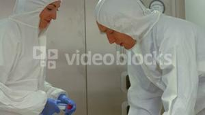 Scientists in protective suits working together