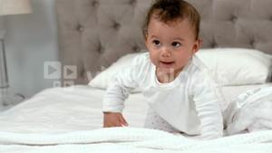 Baby in white clothes crawling