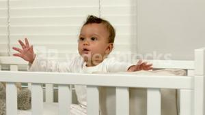 Cute baby sitting in his crib