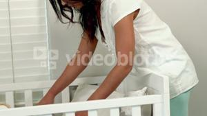 Mother tidying up her baby crib
