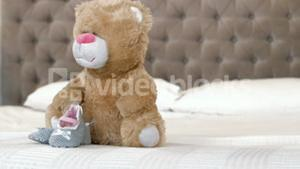 Baby shoes and teddy bear on bed