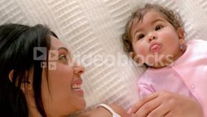 Loving mother with baby in bed