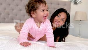 Mother playing with baby daughter on bed