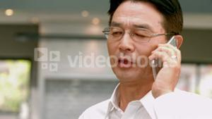Asian businessman phoning in the kitchen