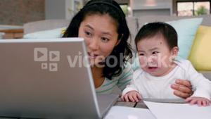 Mother with crying baby using laptop