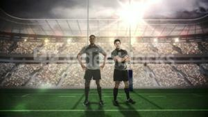 Serious rugby players posing in front of goal post