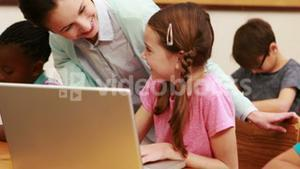 Teacher helping pupil with laptop