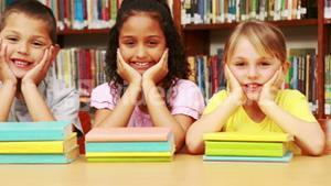 Pupils smiling at camera in library