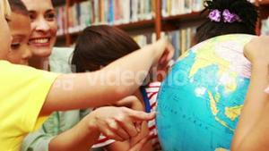 Pupils and teacher looking at globe in library