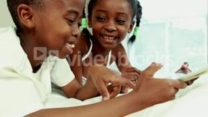 Cute siblings using tablet in bed