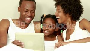 Cute family using tablet in bed