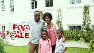 Happy family outside their new home