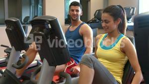 Couple using exercise bikes in gym