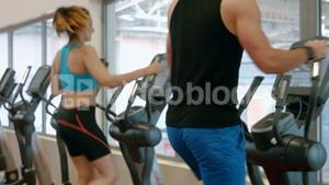Fit couple using cross trainer in gym