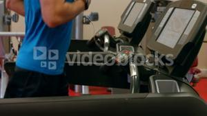 Fit man running on treadmill in gym