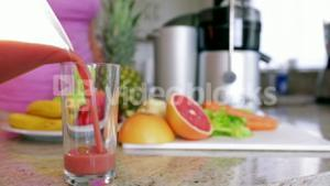 Woman pouring fresh fruit and vegetable juice