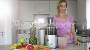 Blonde pouring fresh fruit and vegetable juice