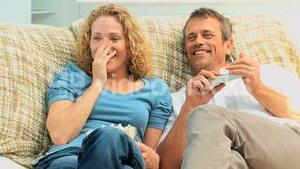 Couple laughing in front of the tv