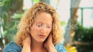 Curly haired woman having a neck pain