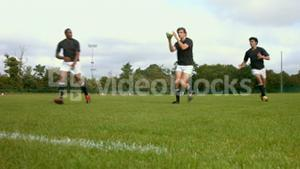 Rugby team members passing the ball