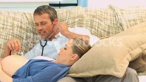 Man listening to the belly of his pregnant wife
