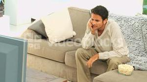 Stressed man getting nervous in front of his tv
