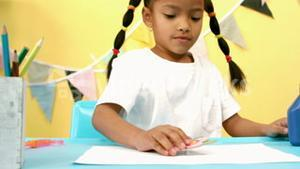 Girl placing flower template on a sheet of paper