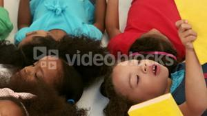 Small group of kids lying down and reading books