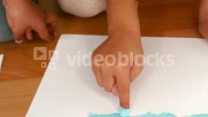 Kids finger painting on sheets of paper
