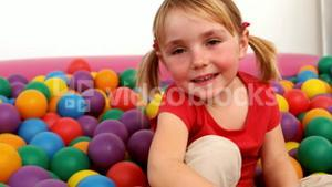 Smiling girl inside a ball pit