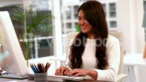 Smiling attractive woman typing on keyboard