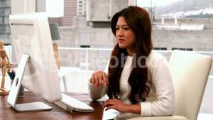 Creative businesswoman typing on computer