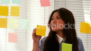 Casual businesswoman writing on post it