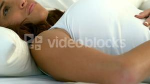 Woman lying in bed rubbing stomach